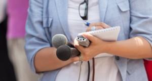Ρεπόρτερ με μαγνητοφωνάκι και μικρόφωνα σημειώνει